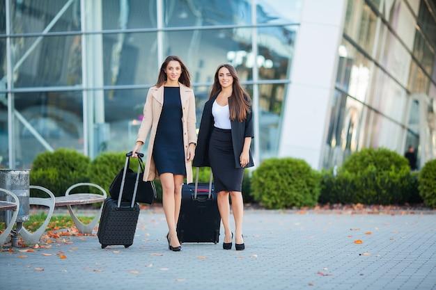 女性の友人は一緒に旅行をしています。空港で荷物を持つかわいいブルネットの正面図