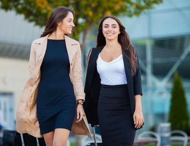 Две счастливые девушки путешествуют вместе за границей с чемоданом в аэропорту