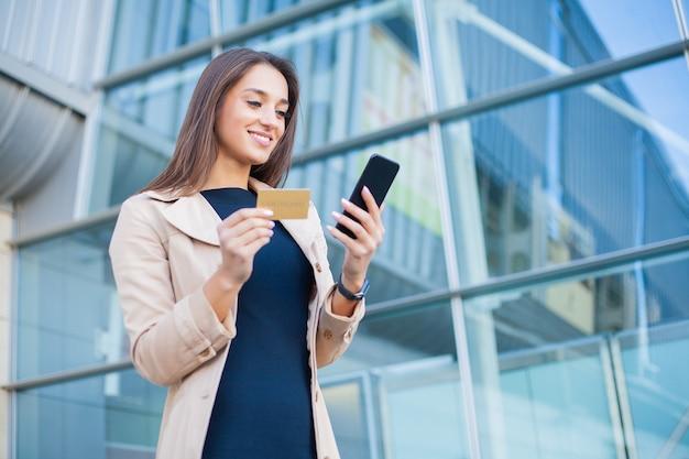 クレジットカードで買い物の女性。電話を使用してゴールドカードと美しい若い女性