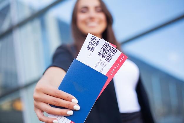 旅行。空港でパスポートと搭乗券を保持している女の子のクローズアップ