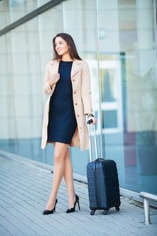 スーツケースを持つ若い陽気な女性。旅行、仕事、ライフスタイルの