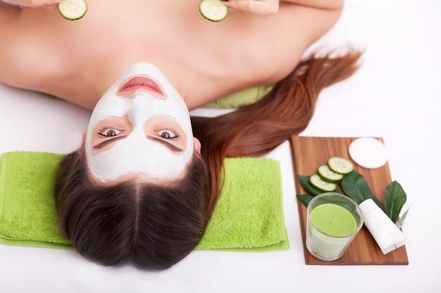 スパスパサロンで女性の顔に栄養マスクを適用する手