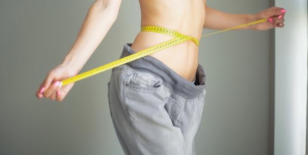 ダイエット。彼女のウエストを測定するスポーツウェアの女性。ダイエット