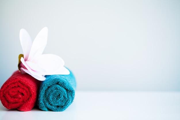 色のタオルとバスルームの背景にコピースペースを持つ白いテーブルの上の蘭。