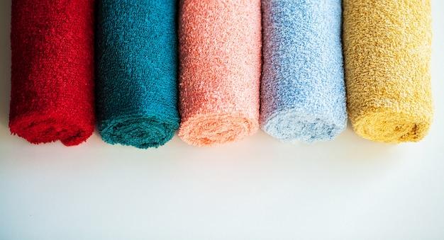 Цветные полотенца на белом столе с копией пространства на фоне ванной комнате.