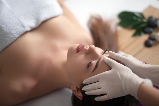 Массаж лица. крупным планом молодой женщины получают санаторно-курортное лечение.