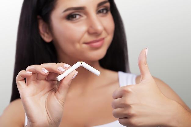 喫煙に対する少女。マクロ撮影。喫煙に反対している若い女の子の手で壊れたタバコ。