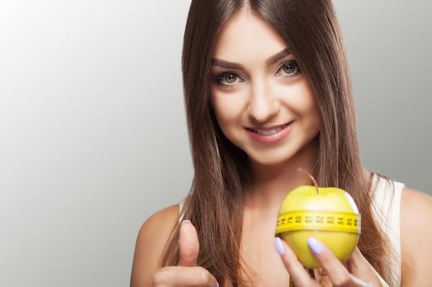 ダイエット。フィットネス若い女の子はダイエットを順守し、測定テープでリンゴを保持しています。体重が減る。