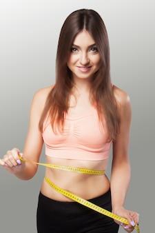 Рацион питания. мера талии ленты. молодая красивая девушка делает измерения своей спортивной фигуры.