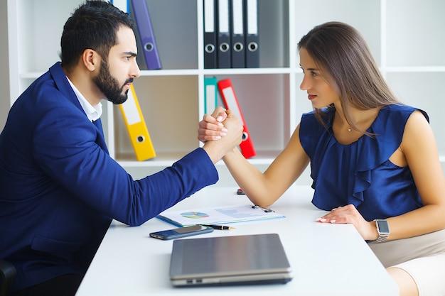 男と女が敵対的な表情でお互いを見つめています。
