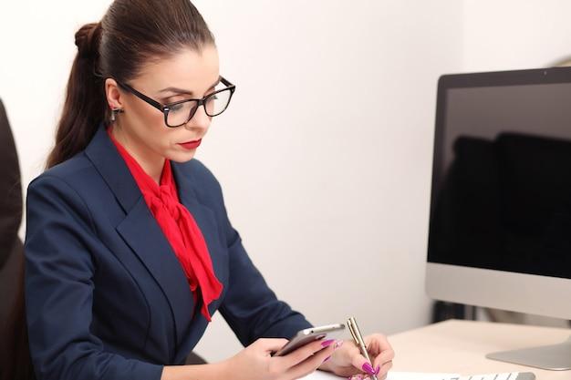 デスクトップに取り組んでいるオフィスの若い女性