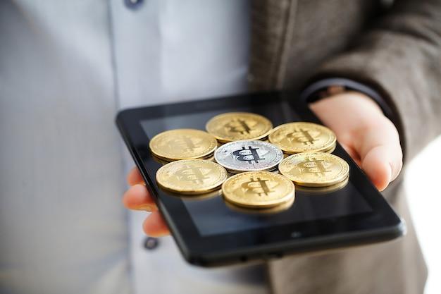 画面上のビットコインとスマートフォンを持っている手。