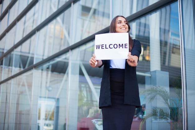 ウェルカムメッセージとポスターの女性ビジネス