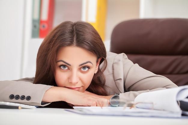 目を閉じて寝ているオフィスの机で若い疲れた女性