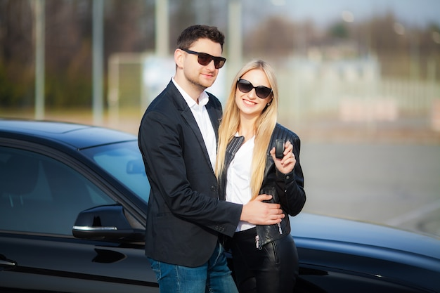 美しいカップルは彼らの新しい車のキーを保持しています。