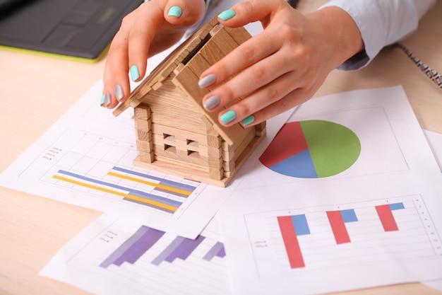 保険および家の保護の概念。女性の手の下の美しい家
