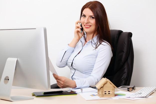ドキュメントとオフィスで働く幸せなビジネス女性