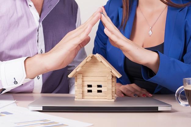 夢のスイートホームのコンセプト。女性は手で家を保持します。あなたの財産