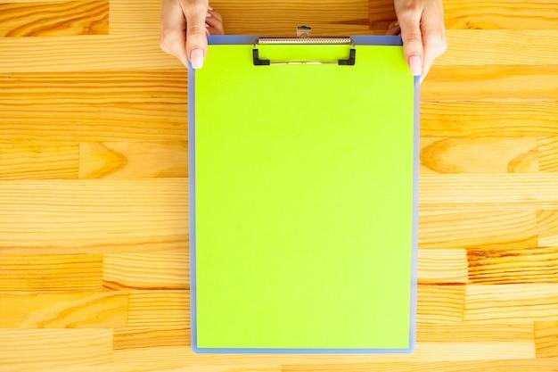 木製のテーブルの背景に緑色の紙のフォルダーを持っているオフィス手
