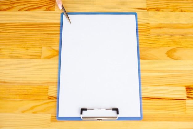 木製のテーブルの背景に赤い色の紙のフォルダーを持っているオフィス手。