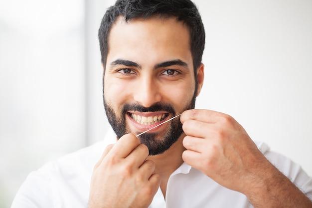 歯の健康。健康的な歯をフロス美しい笑顔を持つ男