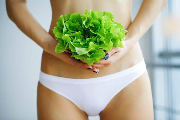 健康。ダイエット。健康的な食事。新鮮な野菜を手で保持しているスリムな女性