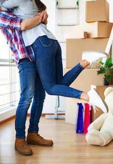 Счастливая молодая пара движется вместе в новой квартире