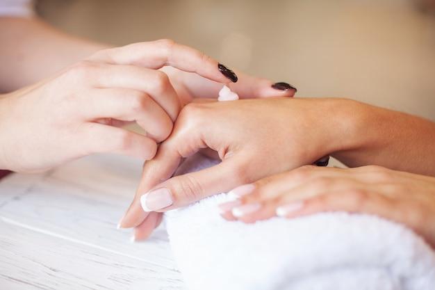 女性の手のケア。手にピーリングスクラブまたは保湿クリームを塗る