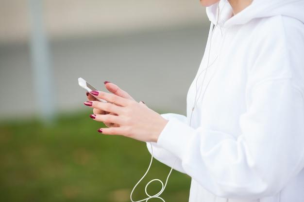 かなり若いスポーツ選手のヘッドフォンを入れて、街で音楽を聴く