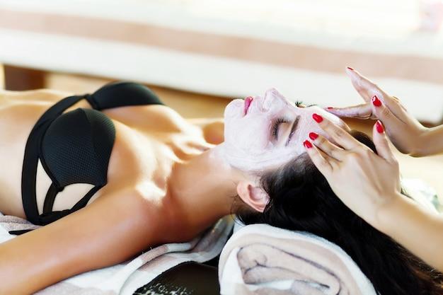美容師は女性の顔に化粧品のマスクを塗る