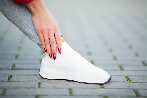 フィットネス。靴ひもを締める女性ランナー。靴の道路のクローズアップで実行されているランナー女性足