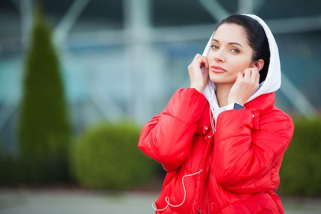 フィットネス。屋外-スポーツと健康的なライフスタイルのコンセプトを行使しながら電話で音楽を聴く女性