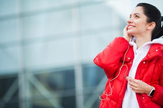 フィットネス。屋外で運動しながら電話で音楽を聴く女性