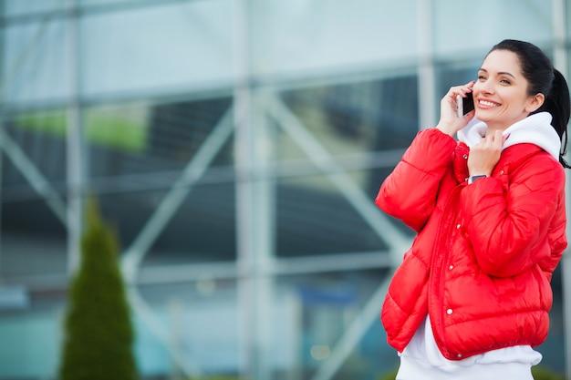 フィットネス女性が休憩、電話で話している-スポーツと健康的なライフスタイルのコンセプト
