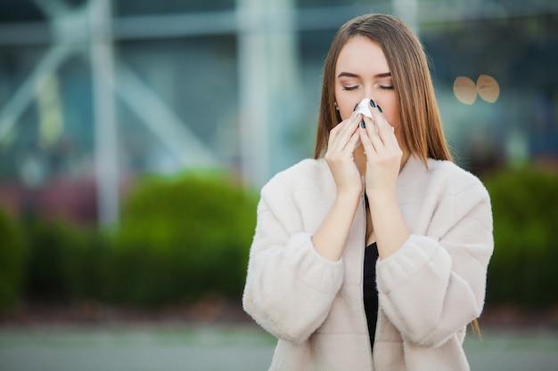 風邪やインフルエンザ。路上で風邪をひいた若い魅力的な女の子は、ナプキンで彼女の鼻を拭きます