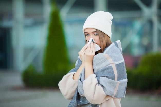 風邪やインフルエンザ。白い組織と屋外の魅力的な若い女性