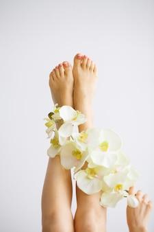 Уход за руками и ногтями. красивые женские ножки с совершенным педикюром. день красоты девушка держит цветы орхидеи. спа маникюр