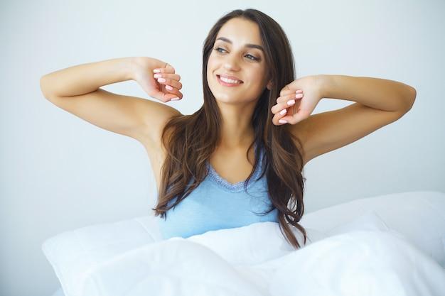美しい女性が目を覚まし、白いベッドの上に座っています。