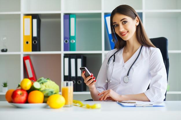 医師はダイエット計画を書き始めます。美しい若い栄養士の笑顔と光と近代的なオフィスで作品。