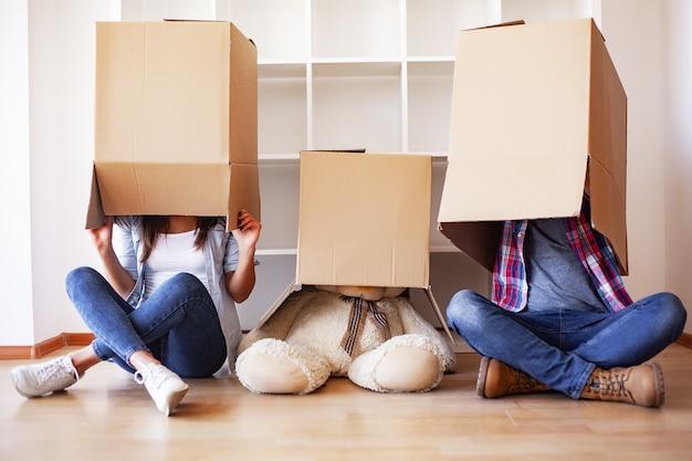 新しい家。面白い若いカップルを楽しみ、新しい家への移動を祝います。新しい家の空の部屋で幸せなカップル