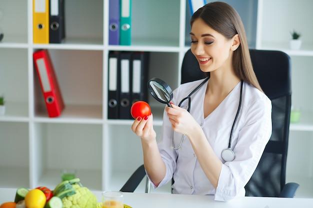 健康。医師はダイエット計画をサインアウトします。栄養士は一握りのフレッシュトマトを保持しています。果物と野菜。オフィスで美しい笑顔で若い医者。
