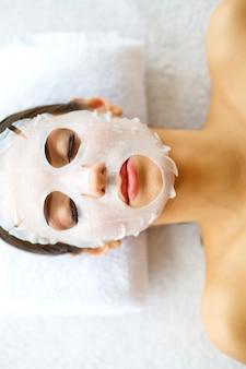 肌とケア。フェイスマスクで横になっている美しい女性。