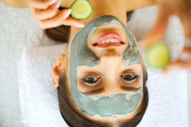 顔にマスクを持つ美しい少女