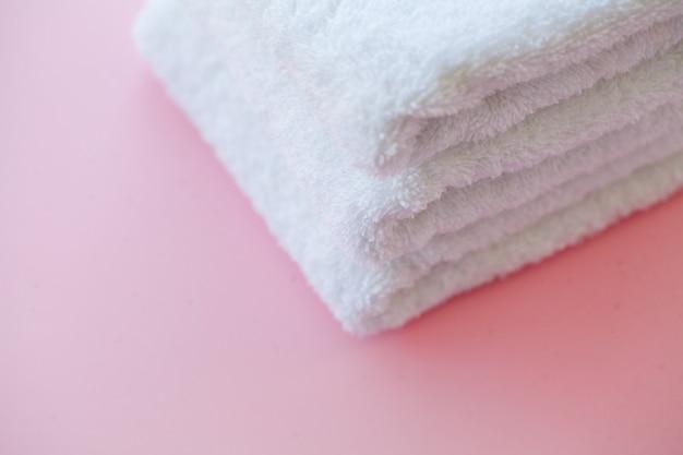 ピンクのテーブルの上の美しいスパ組成白いタオル