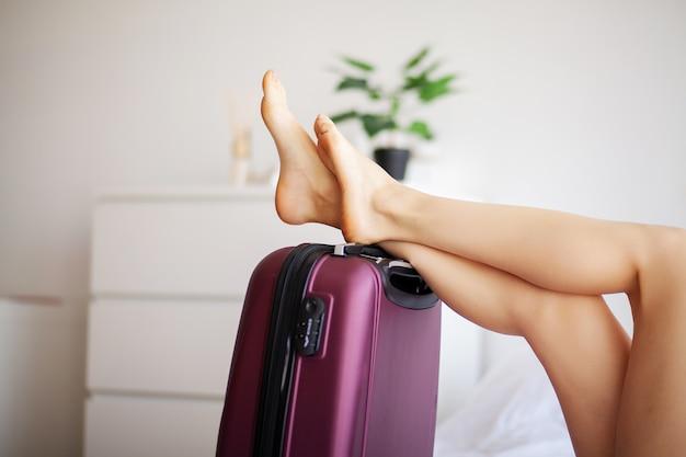 女性の足が荷物で育った、自宅の若い女性がベッドに横たわっています。白い寝室。
