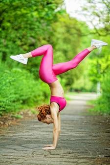 フィットネス。アスリート少女、外で運動選手、女性フィットネス。公園でストレッチ若い美しい女性