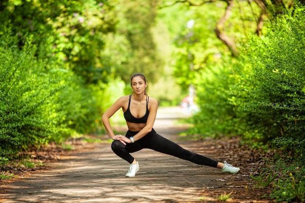 Фитнес. молодая красивая женщина, растяжения в парке