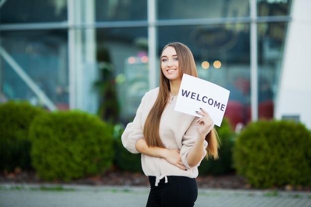 ウェルカムメッセージとプラカードを持つ女性ビジネス