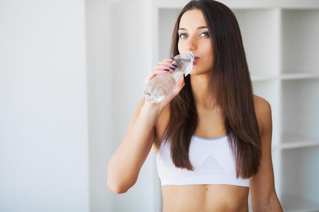 若い女性は水を飲む。水のボトルを保持している美しい若い女の子