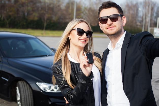 ディーラーへの訪問成功。幸せな若いカップルが選択し、家族のために新しい車を買う